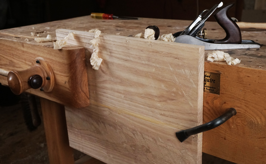 A holdfast in the front apron, or sliding board jack teams up with your face vice to steady wide boards.